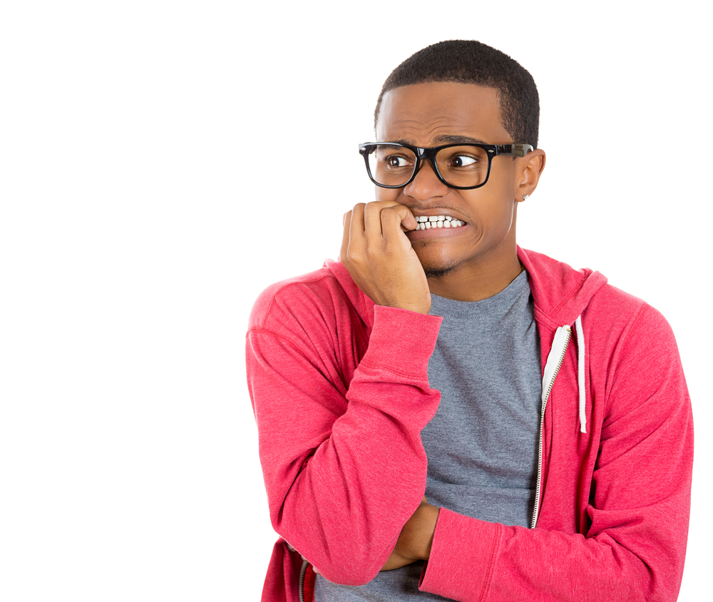 Closeup portrait of nervous, stressed young nerdy guy man in panic and fear, biting fingernails looking anxiously craving something isolated on white background. Negative emotion expression feeling