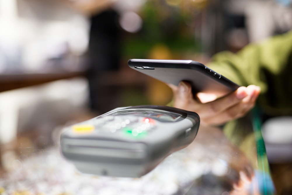 Woman paying with smartphone by NFC-1