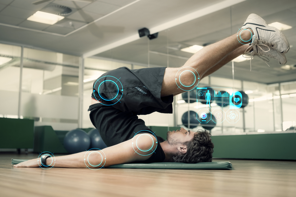 Fit man doing pilates in fitness studio against fitness interface