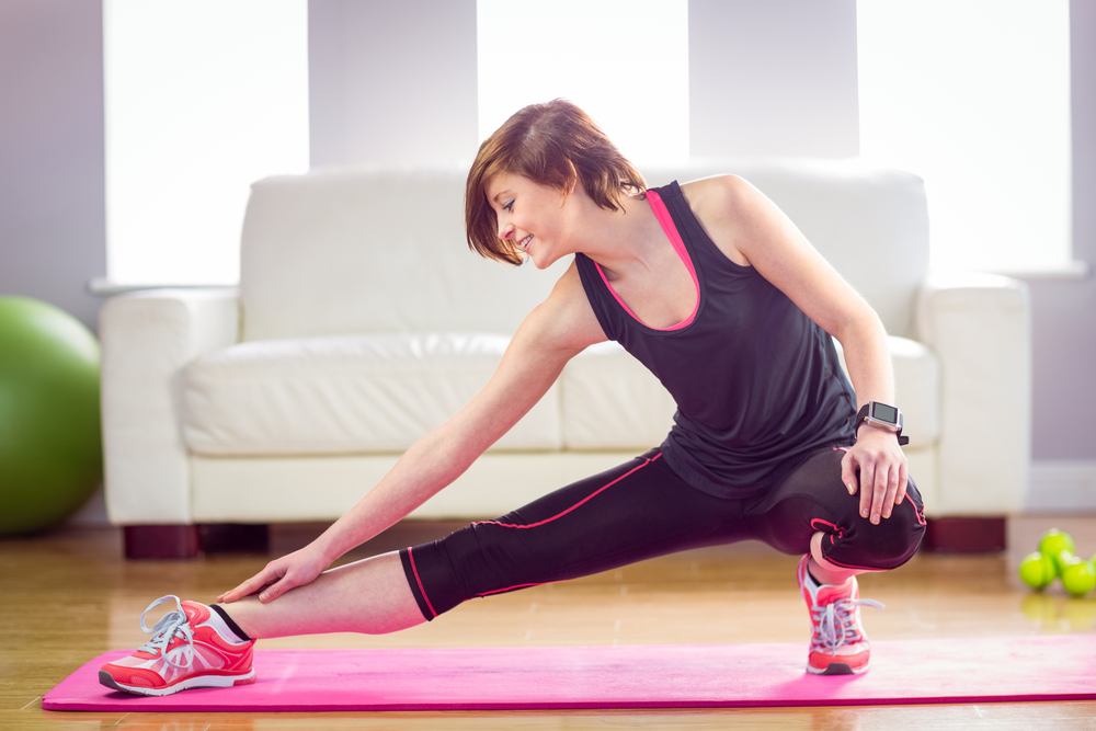 Fit woman stretching on exercise mat at home in the living-room